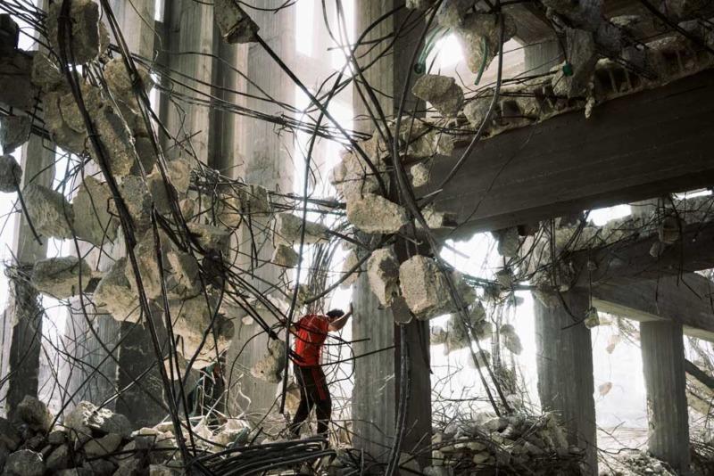 Un lavoratore ricicla barre d'acciaio rinforzate da un edificio che è stato bombardato